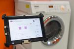 Tablet kommandiert Waschmaschine.