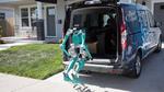 Roboter-Postbote vor dem autonomen Fahrzeug beim Ausladen des Pakets