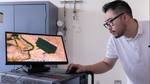 Mikroskopaufnahme eines Mikro-Borsten-Bots, Doktorand Thiian (Chris) Hao mit einem Mikroskopbild