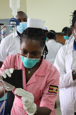 Krankenschwester Winnie Kibirige installiert das Schwerkraftinfusionssysten ECGF-IS für eine Therapie im Rahmen einer klinischen Studie an Erwachsenen am Kiruddu Hospital in Kampala.