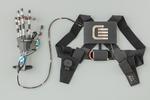 Aufbau des Systems: Der batteriebetriebene Motor im Rucksack bewegt die Finger des Exoskeletts über einen Bowdenzug. Für die bestmögliche Kraftübertragung sorgen 3D-gedruckte Fingerglieder aus Hochleistungskunststoff von Igus.