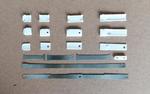 Teile auseinandergebauter Finger. Sie bestehen aus drei übereinander gelegten Blattfedern, zusammengehalten durch Fingerglieder aus robustem und reibungsarmem Hochleistungskunststoff (weiß).